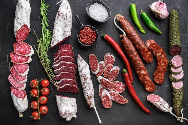 Набор различных испанских сушеных вяленых колбасок салями и целых отрезов на черном фоне, вид сверху.