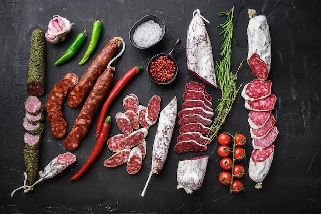 Набор различных испанских колбас салями вяленых ломтиков и целых нарезок на плоской поверхности.
