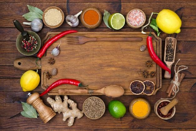 あなたのテキストのためのコピースペースと木製のテーブル上の様々なスパイスとハーブのセット。素朴なスタイルの料理と料理の食材。上面図。