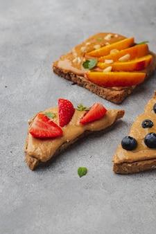 Набор различных тостов с арахисовым маслом; мед; мята; арахис, нектарин, черника и клубника