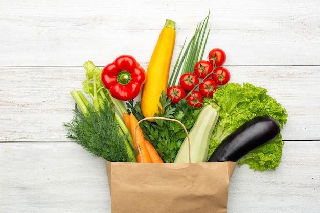 Набор овощей и зелени в бумажном пакете на белом деревянном фоне. здоровая вегетарианская еда.