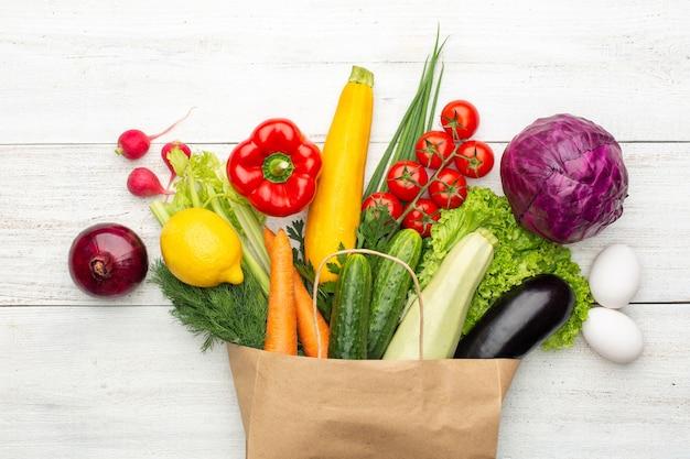 Набор овощей и зелени в бумажном пакете на белом деревянном фоне. покупки в супермаркете или на рынке. вид сверху.