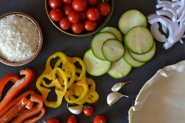 黒の背景に野菜(ピーマン、タマネギ、ズッキーニ、トマト)とparmiganoのセットです。サラダパイの材料。上面図。