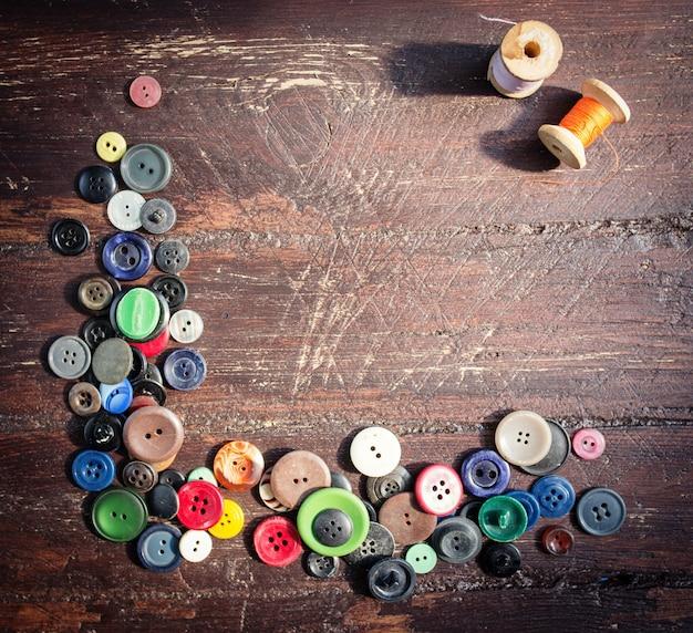 古い木製のテーブルにビンテージ ボタンのセット