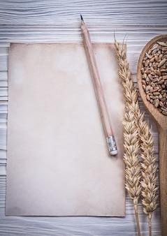 Набор старинных бумажных листов, ржаных ушей, карандаша и деревянной ложки с кукурузой на деревянной доске