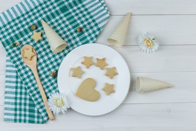 Набор вафельных рожков, цветов и печенья в тарелке и деревянной ложке на деревянном и кухонном полотенце. плоская планировка.