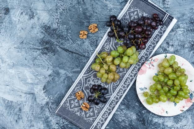 グランジとキッチンタオルの背景のプレートにクルミとブドウのセット。上面図。