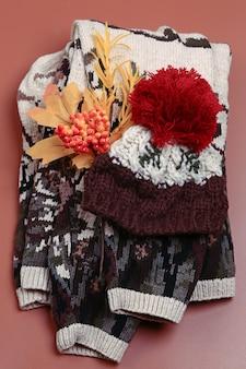 ベージュの背景に暖かい秋の服のセットトップビューニットセーターとウールの帽子フラットスタイル...