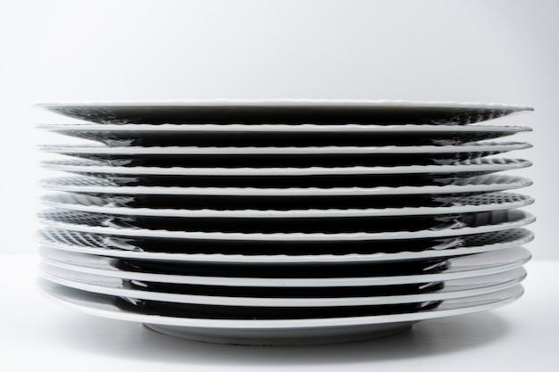 白いテーブルの上に洗った積み重ねられた白い皿のセット。