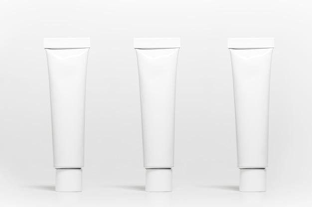 白いスタジオの表面に分離された白いアルミニウム歯磨き粉チューブのセット