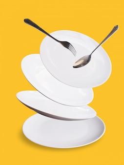 Набор белой керамической тарелки или тарелки вилка и ложка, изолированные на желтой стене.