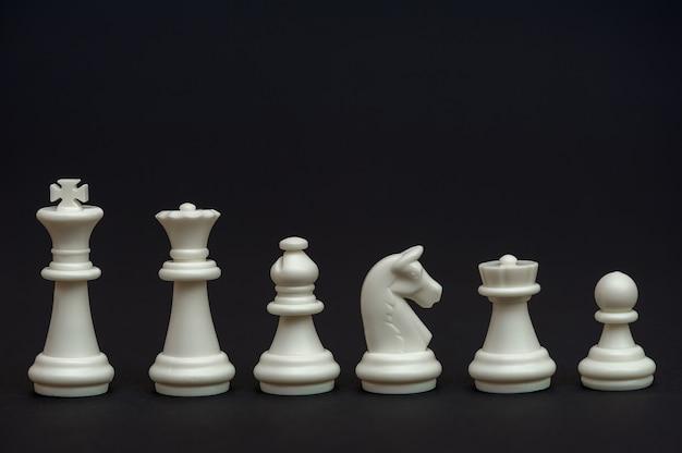 검정색 배경에 흰색 체스 조각 세트 chessmen table game