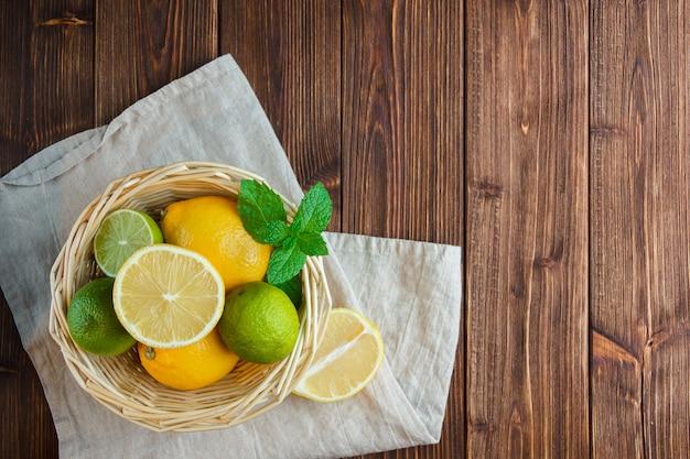 Набор белой ткани и лимонов в корзине на деревянном фоне. вид сверху.