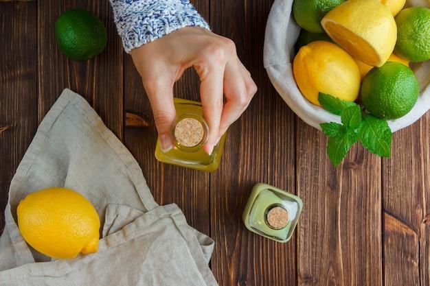 白い布のセット、木の表面のバスケットにレモンジュースボトルとレモンを保持している手。上面図。