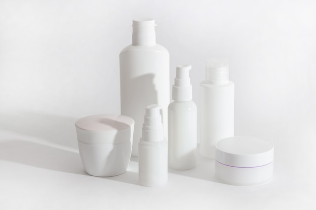 白い化粧品のボトルとハードシャドウの瓶のセット。ホームとビューティーサロンケアのコンセプト