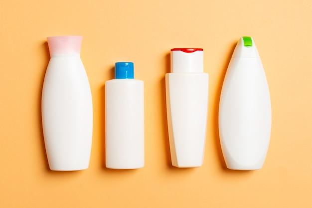 色付きの背景、コピースペースと上面図に分離された白い化粧品コンテナのセット。あなたが設計するための空きスペースを持つプラスチック製のボディケアボトルコンテナのグループ。