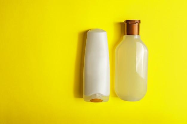 Комплект белых косметических контейнеров на желтой предпосылке, взгляд сверху с космосом экземпляра.