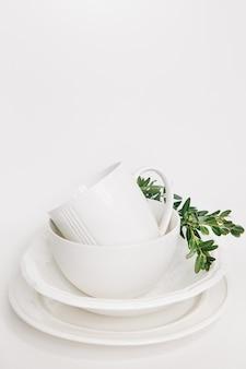 Набор белых блюд из трех тарелок и чашка, украшенная ветвью эвкалипта