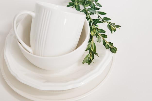 3つのプレートとユーカリの枝で飾られたカップの白い皿のセット