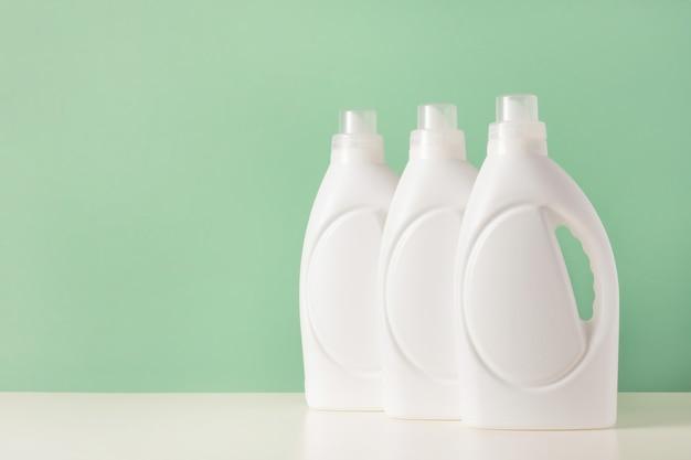 액체 세탁 세제 또는 세제 또는 표백제 또는 섬유 유연제의 흰색 플라스틱 병 세트. 녹색 배경에 바이오 세척 제품을 위한 빈 모형 포장. 빨래하는 날