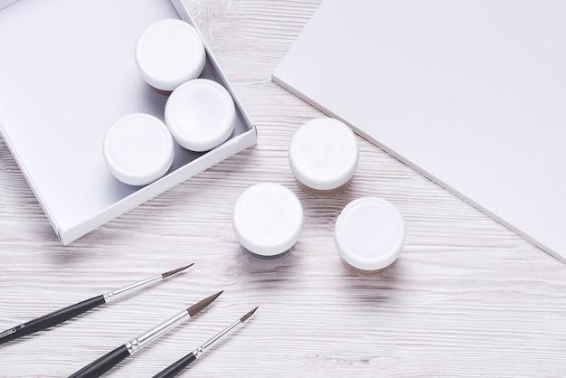 木製のテーブルの上に、カバー付きの白いプラスチック缶のセット