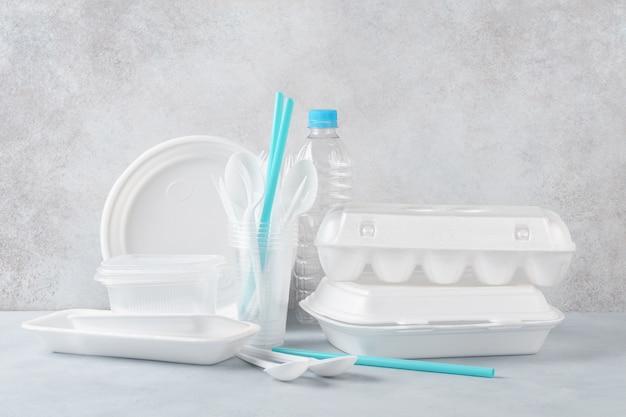 白いプラスチックの使い捨て食器と包装のセット。様々な食器。コピースペース。