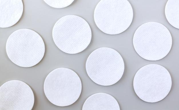 회색 테이블 위에 흰색 소프트 클렌징 코튼 패드 또는 디스크 세트