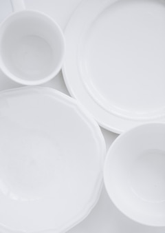 Set of white utensils from three different plates and a cup on a white background