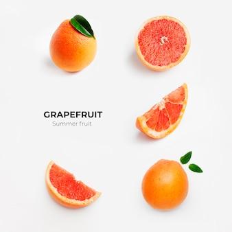 Набор целых и нарезанных свежих грейпфрутов и ломтиков, изолированных на белой поверхности