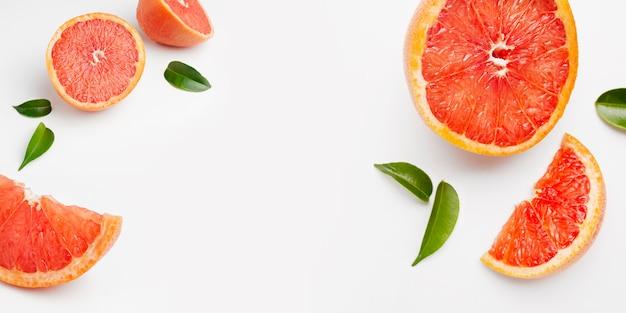 全体とカットフレッシュグレープフルーツとスライスの白い表面に分離