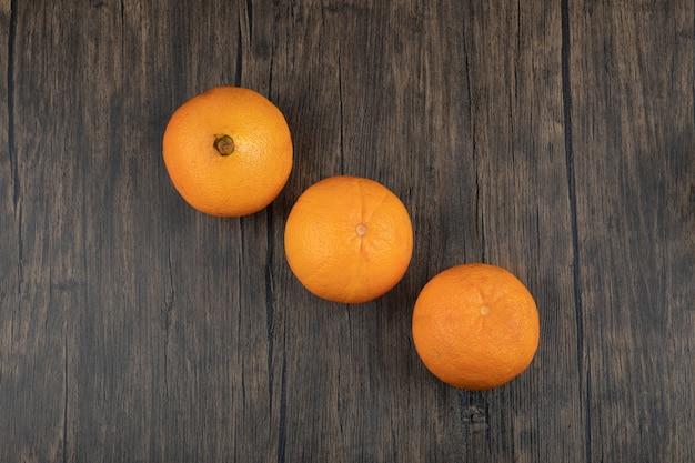 Набор целых здоровых оранжевых фруктов на деревянном столе.