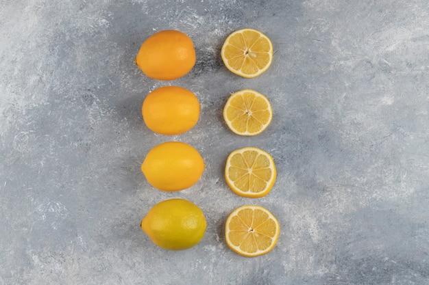 Набор целых кислых лимонов с кусочками на мраморе.