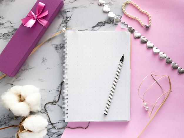 女性のアクセサリーデスク-ペン、ギフト、ジュエリー、ブレスレット、ピンクの大理石の背景、上面に綿の花とノートのセット