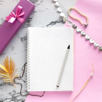 女性のアクセサリーデスク-ペン、ギフト、ジュエリー、ブレスレット、ピンクの大理石の背景、トップビューで黄金のヤシの葉とノートブックのセット