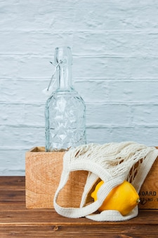 木製と白の表面に木枠、空のボトル、レモンのセット。側面図。テキスト用のスペース