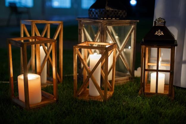 Набор деревянных фонарей с огнем крупным планом. деревянные подсвечники