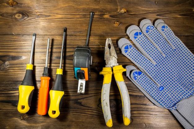 나무 배경에 작업 도구 세트 스크루드라이버 테이프 측정 펜치 및 장갑