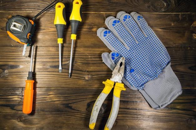 나무 배경에 작업 도구 집합입니다. 나무 표면에 드라이버, 줄자, 펜치 및 장갑