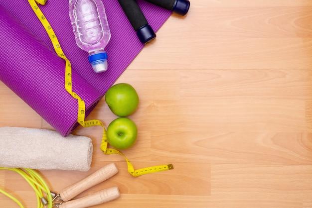 보라색 매트와 아령, 수건 및 물 병 요가 연습 세트