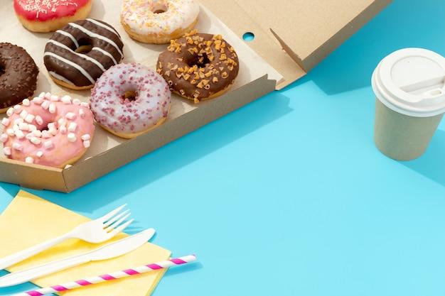青い表面の紙箱においしいカラフルなドーナツのセット