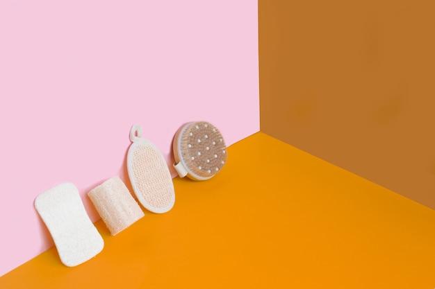 Набор предметов первой необходимости для ванной комнаты с нулевыми отходами на цветной стене.