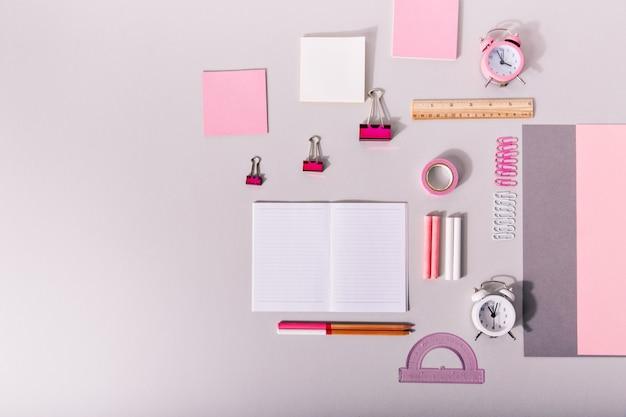 Set di forniture per ufficio per il lavoro in colori rosa pastello sulla parete isolata