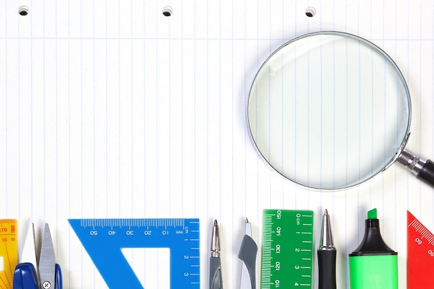 A set of office tools on the notebook to take notes. frame for records and magnifier.