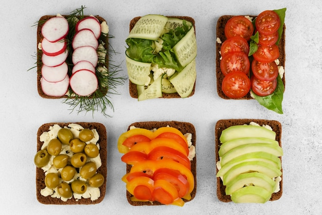 Set of open faced sandwiches on white stone background. vegetarian vegetables sandwiches with cheese, radish with dill, olives, tomato with basil, pepper, avocado and cucumber with salad. top view.