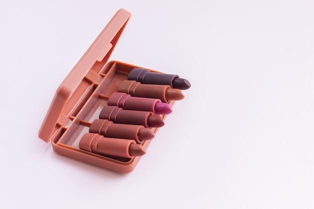 Набор или палитра помад на светло-розовом фоне. концепция роскошных косметических продуктов