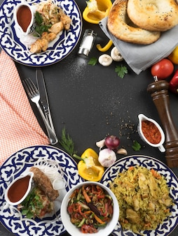 A set of oriental dishes in plates with traditional uzbek ornaments - pilaf with chicken, shish kebab, lula kebab, tandoor tortilla, adjika, vegetables and spices.