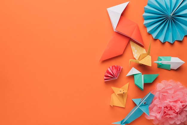 Set of origami paper art craft on bright orange surface