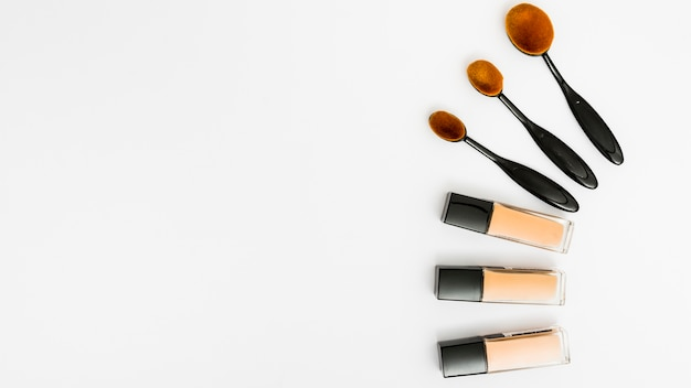 Set of oval makeup brushes with liquid foundation bottles on white backdrop