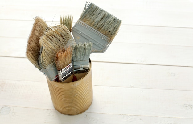 Set of paint brushes on wooden floor