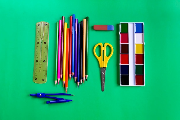 A set of paints, pencils, scissors, ruler, eraser and compasses on green